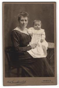 Fotografie Josef Gerschkowitsch, Wien, Portrait lächelnde Mutter mit Kleinkind im Arm auf Stuhl sitzend