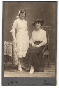 Fotografie Atelier Fortuna, Wien, Portrait Dame in weisser Bluse mit Hut auf Stuhl sitzend u. junge Frau im weissen Kleid