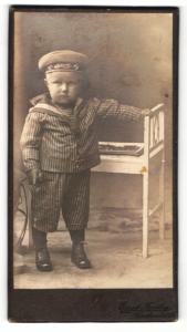 Fotografie Ernst Freitag, Finsterwalde, Portrait kleiner niedlicher Bube mit Mütze im Matrosenanzug
