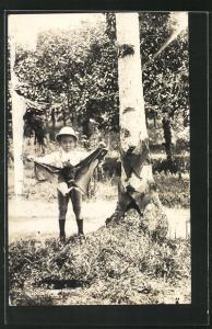 AK Singapore, kleiner Junge mit gefangener Fledermaus