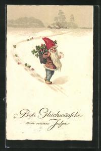 AK Zwerg stapft mit einem Korb voller Klee und Fliegenpilzen durch den Schnee, Glückwünsche zum neuen Jahre
