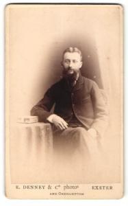 Fotografie E. Denney & Co., Exeter, Mann im Anzug im Stuhl sitzend mit Vollbart und Arm auf Tisch