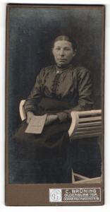 Fotografie C. Brüning, Oldenburg i / Gr., Portrait ältere Dame in hübscher Kleidung mit Heft auf Stuhl sitzend
