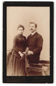 Fotografie Rud. Conrad, Berlin, Mann im Anzug mit Schnurrbart und Frau im Kleid mit Halskette und Amulett daran
