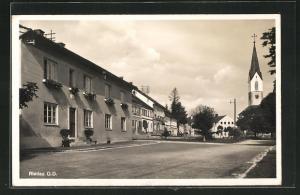 AK Riedau, Strassenpartie mit Blick zur Kirche, Plakette mit  über der Haustür