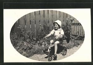 Foto-AK Kleiner Bub auf Dreirad im Garten