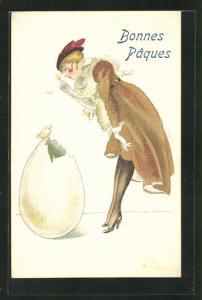 AK Art Deco, Dame schaut mit Lorgnon auf ein kleines Küken auf einem grossen Ei