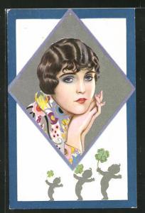 AK Art Deco, Dame mit schwarzen Haaren und träumerischer Pose in bunter Bluse, Kinder mit Kleeblättern