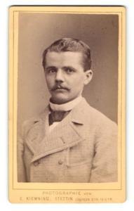 Fotografie E. Kiewning, Stettin, Portrait junger Mann mit Schnauzbart im Mantel