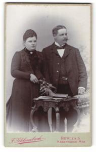 Fotografie F. Schloenbach, Berlin-S., Portrait bürgerliches Paar in eleganter Kleidung mit Blumen