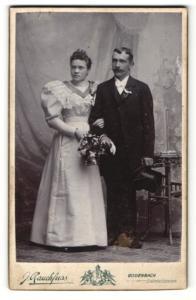 Fotografie J. Rauchfuss, Bodenbach, Portrait bürgerliches Paar in hübscher Hochzeitskleidung mit Blumenstrauss