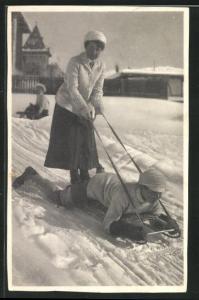 AK Mann liegt bäuchlings auf Schlitten und Frau hält die Riemen
