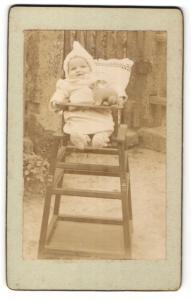 Fotografie unbekannter Fotograf und Ort, Portrait Säugling in Kindersitz mit Spielzeugkaninchen