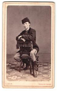 Fotografie L. Colin, Chaux de Fonds, Portrait junger Herr in traditioneller Kleidung mit Fellmütze
