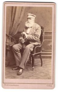 Fotografie Ferd. Grundmann, Gotha, Portrait betagter Herr mit Rauschebart und Tellermütze