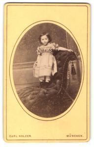 Fotografie Carl Holzer, München, Portrait kleines Mädchen im hübschen Kleid auf Sessel stehend