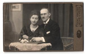 Fotografie Karl Kruse, Burg s/MGDB, Mann im Anzug mit Brille zusammen mit Frau im Kleid mit Halskette und Amulett