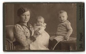 Fotografie Jul. Pingel, Nordenham a. W., Frau im Kleid mit Baby im Arm und Junge auf Tisch sitzend