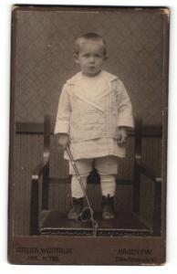 Fotografie Atelier Westfalia, Hagen i. W., Portrait frecher blonder Bube mit Stab und Seil