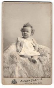 Fotografie Atelier Blesius, Hameln i. W., Portrait lachendes kleines Mädchen mit lockigem Haar auf Fell sitzend
