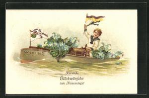 Präge-AK Namenstag, Knabe im Matrosenanzug sitzt im Ruderboot Wilhelm II, geschmückt mit Blumen und Flagge