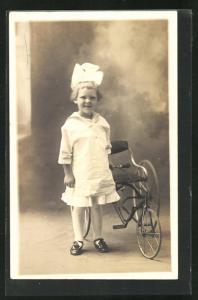 AK Spielzeug, kleines Mädchen mit Schleife im Haar und Dreirad