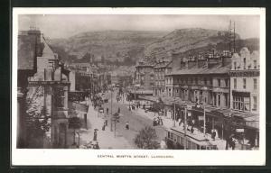 AK Llandudno, Central Mostyn Street, Strassenbahn und Häuserfassaden mit Blick auf Berge, Restaurant