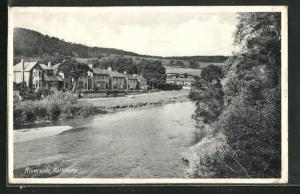 AK Rothbury, Riverside, Blick auf Häuserzeilen am Fluss mit Landschaft