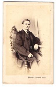 Fotografie Lutze & Witte, Berlin, Portrait junger Herr in eleganter Kleidung am Tisch sitzend