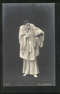 AK Harlekin betrachtet ein Paar Damenschuhe, L`Envie