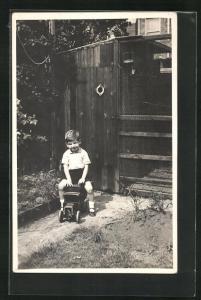 Foto-AK Kleiner Junge auf einem Spielzeugauto