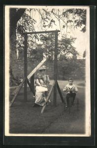 Foto-AK Mutter sitzt mit Mädchen auf der Schaukel, Junge fährt Dreirad