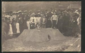 AK Sandplastik, grosse Sandburg mit Fahne und Publikum am Strand