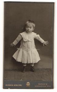Fotografie Globus Atelier, Berlin, Kleinkind in weissem Kleid lehnend an Wand