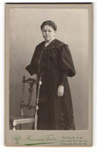 Fotografie Hermann Tietz, Berlin, Portrait dunkelhaarige junge Schönheit im schwarzen prachtvollen Kleid