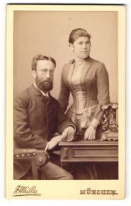 Fotografie F. Müller, München, Portrait elegant gekleidetes Paar am Tisch stehend