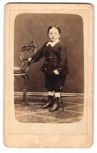 Fotografie H. A. K. Ringler, Leeuwarden, Portrait niedlicher Bube am Stuhl stehend