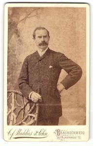 Fotografie C.F. Beddies & Sohn, Braunschweig, Portrait Herr im feinen Anzug an einem Stuhl