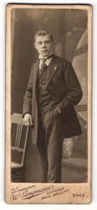 Fotografie W. Langmann, Saaz, Portrait junger Mann im Anzug an einem Stuhl