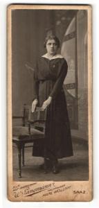 Fotografie W. Langmann, Saaz, Portrait Dame im schwarzen Kleid an einem Stuhl