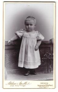Fotografie Atelier Apollo, Dresden, Portrait Kleinkind mit kurzem Haar in weissem Kleid