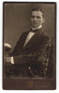 Fotografie Karl Mäckel, Burgstädt, Portrait junger Mann im Anzug auf einem Stuhl
