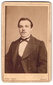 Fotografie Franz Kohn, Zerbst, Mann im Mantel mit schmaler Fliege und Oberlippenbart