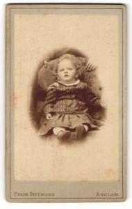 Fotografie Franz Dittmann, Anclam, Kleinkind im gestreiften Kleidchen sitzt auf Sessel