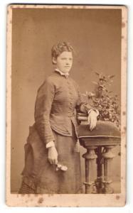Fotografie M. Wehle, Dresden, Frau im Kleid mit Blume in der Hand und auf Bücher gestützt