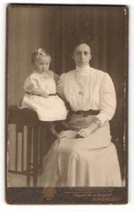 Fotografie R. Rosenkranz, Mügeln, Frau im Kleid sitzend mit Kind auf Tisch sitzend neben sich