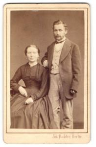 Fotografie Joh. Richter, Berlin, Mann im Anzug stehend hinter Frau im Kleid sitzend