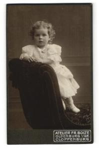 Fotografie Fr. Bolte, Oldenburg i/Gr., kleines Mädchen im Kleid auf Sessel stehend an Lehne gestützt