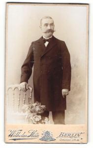 Fotografie Wilhelm Stein, Berlin, Mann im Anzug stehend mit Fliege und breitem Schnauzer