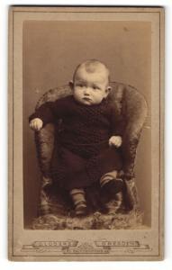 Fotografie G. Luders, Dresden, Kleinkind im Kleidchen in Sessel stehend